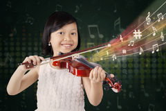 Girl playing a song with a violin. Cute girl smiling at the camera while playing a song with a violin Royalty Free Stock Image
