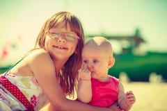 Toddler girl hugging little sister on beach. stock images