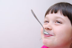 Girl playing with a spoon Stock Image