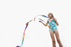 Girl Playing With Stick Streamer Against Sky Royalty Free Stock Photography