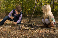 Girl playing with sticks next to her brother Stock Photos