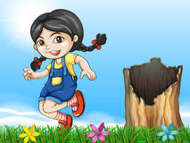 A girl playing beside the stump Stock Photo
