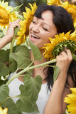 Girl playing with sunflowers in field Royalty Free Stock Images