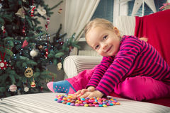 Girl playing with sweets on xmas eve Stock Images