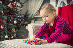 Girl playing with sweets on xmas eve Stock Photography