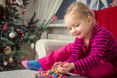 Girl playing with sweets on xmas eve Royalty Free Stock Images