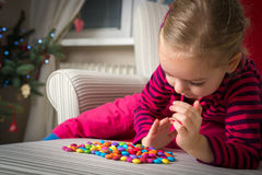 Girl playing with sweets on xmas eve Royalty Free Stock Photography
