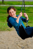 Girl playing on a swing. Stock Photo