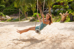 Girl playing the swing on beach Stock Photos