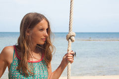 Girl playing the swing on beach Stock Photography