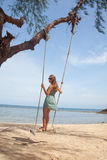 Girl playing the swing on beach Stock Image