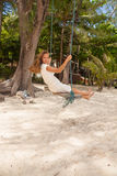 Girl playing the swing on beach Royalty Free Stock Photography