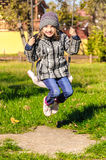 Girl playing in swing in park Stock Photos
