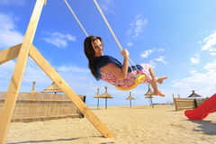 Girl playing on a swing-set. On the beach Royalty Free Stock Photo