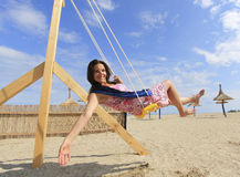 Girl playing on a swing-set. On the beach stock photo