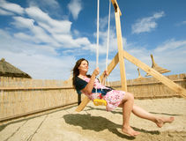 Girl playing on a swing-set Stock Photos