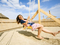 Girl playing on a swing-set Royalty Free Stock Images