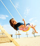 Girl playing on a swing-set. On the beach stock images