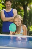 Girl (7-9) playing table tennis with father in background. Royalty Free Stock Photos