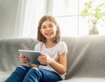 Girl playing with tablet Stock Images