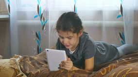 Girl playing in the tablet lies on a bed indoors stock video