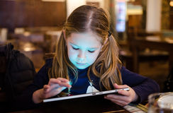 Girl playing on tablet Stock Photo