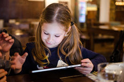 Girl playing on tablet Royalty Free Stock Photo
