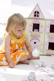 Girl playing tea party. A little 4 year old girl having a tea party playing with her teapot set in front of a wooden dollhouse Stock Image