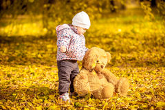 Girl playing with teddy bear at autumn park Royalty Free Stock Photography