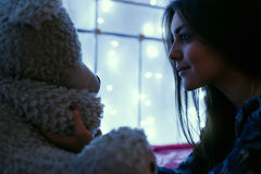 Girl playing with teddy bear in bed before going to sleep. Girl playing with teddy bear in bed Royalty Free Stock Photos