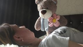 Girl is playing with a teddy bear and smiling while sitting on her bed at home stock video footage