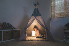 Girl playing in the teepee stock images