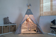 Girl playing in the teepee stock photos