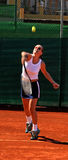Girl playing tennis. In the sun. Serving the ball on a red asphalt court in Spain stock images