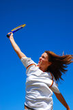 Girl playing tennis. A beautiful caucasian teenage girl playing tennis in front of blue sky background outdoors Stock Photography
