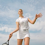 Girl playing tennis on background of sky Royalty Free Stock Image