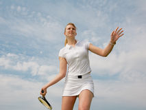 Girl playing tennis on background of sky. Young blond  tennis-player with tennis racket in white sportwear is playing on background of sky Royalty Free Stock Images