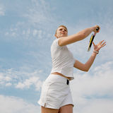 Girl playing tennis on background of sky. Young blond  tennis-player with tennis racket in white sportwear is playing on background of sky Stock Photo