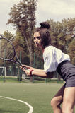 Girl playing tennis on green court Royalty Free Stock Photo