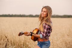 Free Girl Playing The Guitar In A Wheat Field Royalty Free Stock Photos - 53828408