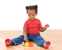 Girl playing with three ducks of plastic. Beautiful african girl playing with three ducks of plastic royalty free stock images