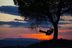 Girl playing on a tire swing. Silhouette of happy young woman on a swing with sunset background Stock Image