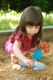 The girl playing to a sandbox Stock Photos