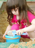 The girl playing to a sandbox. Caucasian the child, park of rest Royalty Free Stock Image