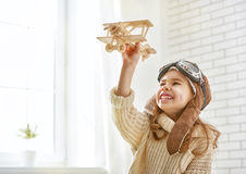 Girl playing with toy airplane. Happy child girl playing with toy airplane. the dream of becoming a pilot Stock Photos