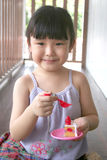 Girl playing toy cake. Girl holding toy fork & cake royalty free stock photography