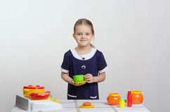 Girl playing toy dishes Stock Image