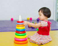 Girl playing toy on floor Stock Image