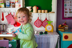 Girl playing in toy kitchen Royalty Free Stock Images