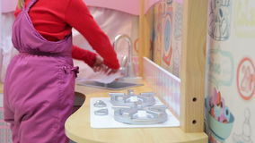 Girl playing with a toy kitchen turns on a gas stove and washes his hands under the tap. In the play area of the mall stock video
